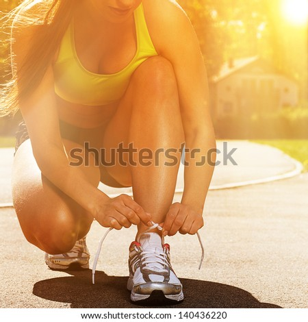 Beautiful young woman in fitness wear ties shoelaces outdoors - stock photo