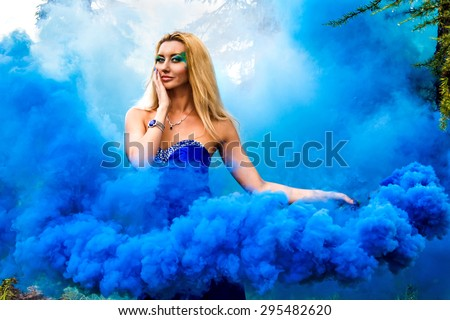 Beautiful young woman in forest in cloud of a bright blue smoke - stock photo