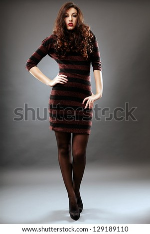 Beautiful young woman in glamour full length pose, over gray background, hand on waist
