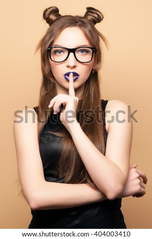 Beautiful young woman in glasses. Cut girl. Spring-summer outfit. Hairstyle Coachella. Short Sexy Shorts. Dark blue lipstick. Fashionable  woman . Yellow background. Toned image.