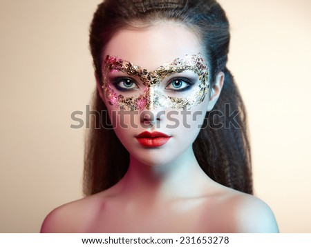 Beautiful young woman in gold mysterious mask. Perfect makeup. Fashion photo - stock photo