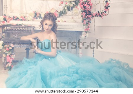Beautiful young woman in gorgeous blue long dress like Cinderella with perfect make-up and hair style sitting near white piano - stock photo