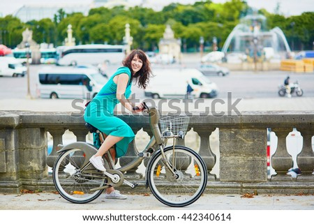 Beautiful young woman in green dress riding a bicycle on a street of Paris