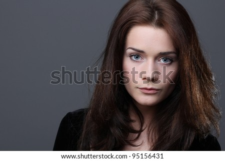 Beautiful young woman in grey background - stock photo