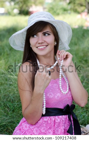 beautiful young woman in hat enjoys summer in the park