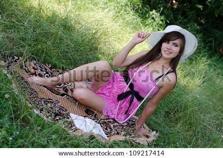 beautiful young woman in hat enjoys summer in the park - stock photo