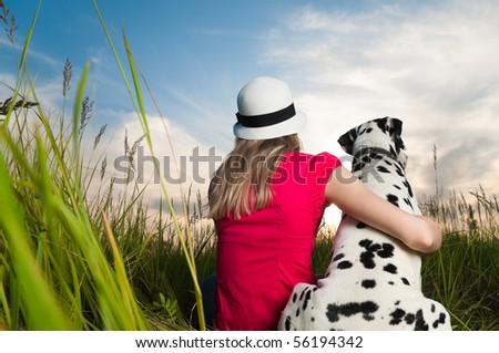 beautiful young woman in hat sitting in grass with her dalmatian dog pet with their backs to camera. Sunset cloudy sky in background and green grass in foreground. - stock photo