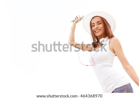 Beautiful young woman in hat with the headset dancing and holding a phone. Summer holidays and vacation concept.