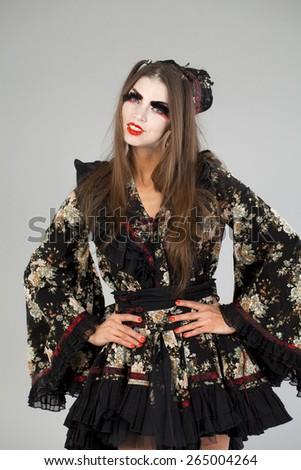 Beautiful young woman in  kimono dress on gray background  - stock photo