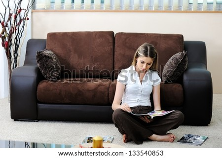 Beautiful young woman in living room on sofa reading newspapers
