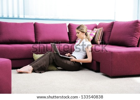 Beautiful young woman in living room on sofa using laptop - stock photo