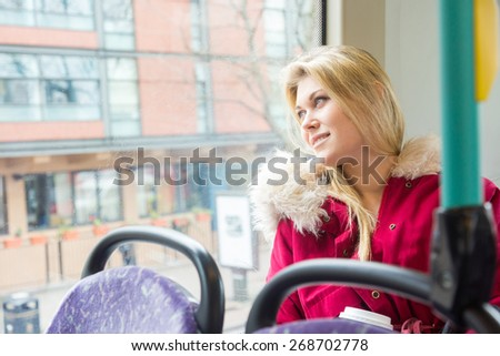 Beautiful young woman in London on a double-decker bus. She is sitting next to the window and looking out, with buildings and traffic on background. - stock photo