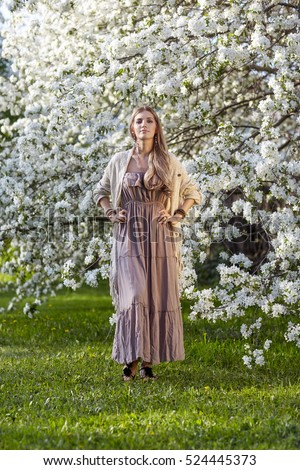 Beautiful young woman in long dress boho style on green grass under apple tree in blossom in Spring garden