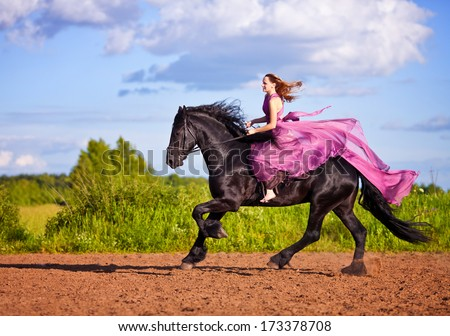 Beautiful young woman in long red dress riding a horse in countryside - stock photo