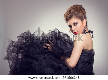 Beautiful young woman in luxurious black dress. Fashion photo. - stock photo
