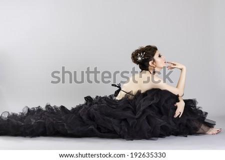 Beautiful young woman in luxurious long black dress.Fashion photo. - stock photo