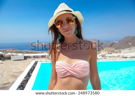 Beautiful young woman in luxury quiet swimming pool - stock photo