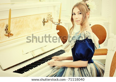 Beautiful young woman in medieval era dress playing the piano.