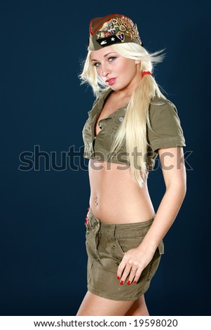 Beautiful young woman in military clothes on dark blue background