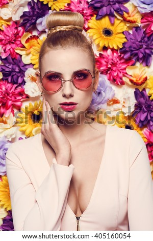 Beautiful young woman in nice dress, pink glasses posing on colorful wall of flowers. Fashion spring photo, nice hair