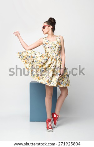 beautiful young woman in nice spring dress, flower pattern posing in studio. Fashion photo - stock photo