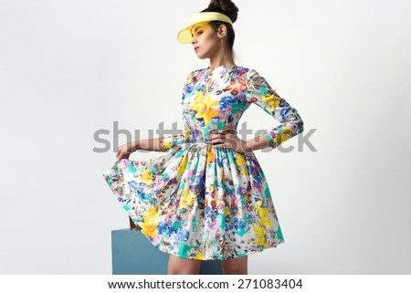 beautiful young woman in nice spring dress, posing in studio, plastic visor. Fashion photo - stock photo