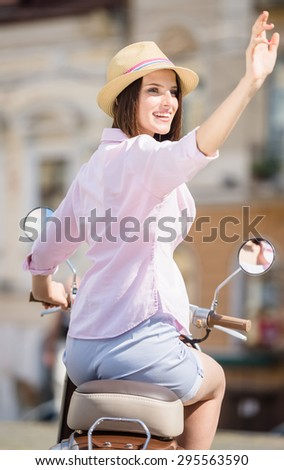 Beautiful young woman in nifty hat sitting on scooter and smiling. - stock photo
