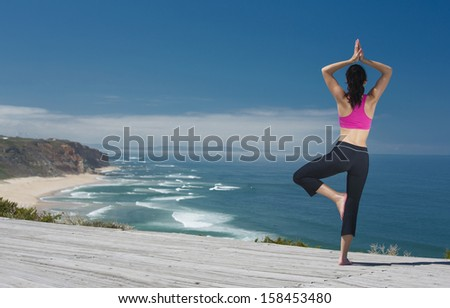 Beautiful young woman in outdoor doing yoga - stock photo