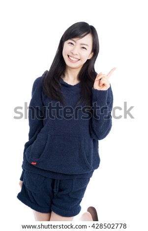 Beautiful young woman in pajamas showing copy space isolated on white background - stock photo