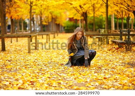 Beautiful young woman in Paris gathering fall leaves in park on a beautiful colorful autumn day - stock photo