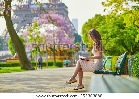 Beautiful young woman in Paris, near the Eiffel tower on a nice and sunny spring day, reading on the bench outdoors - stock photo