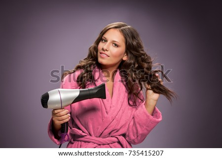 beautiful young woman in pink bathrobe drying hairstyle, cute young lady smiling