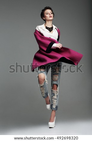 Beautiful young woman in pink coat posing in studio full-length.