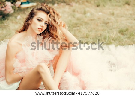 Beautiful young woman in pink glamour dress with long curly hair sitting on green grass in spring sunny day