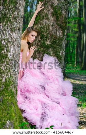 Beautiful young woman in pink glamour dress with long curly hair sitting on tree in sunny forest