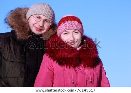 beautiful young woman in pink jacket and man in glasses at winter outdoors, focus on woman - stock photo