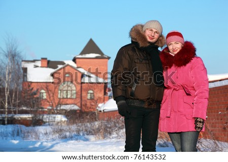 beautiful young woman in pink jacket and man in glasses standing outdoors at winter, house - stock photo