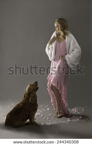Beautiful young woman in pink with white fur coat, wearing red lipstick, black eyeliner and her blonde hair in side swept curls, looking down at her dog - stock photo
