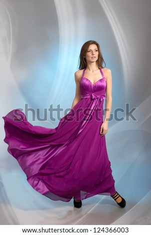 Beautiful young woman in plum violet evening dress, on grey background