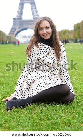 Beautiful young woman in polka dot trench sitting on grass near the Eiffel Tower - stock photo