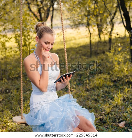Beautiful young woman in prom dress sitting on swings and typing on tablet pc on green summer or autumn outdoors copyspace background - stock photo