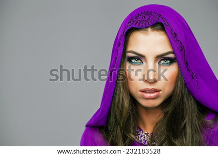 Beautiful young woman in purple  tunic Arabic, on gray background