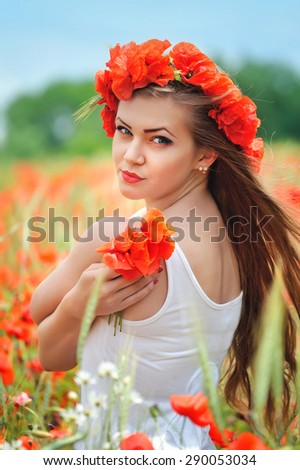 Beautiful young woman in red bright poppy field. Summer portrait - stock photo