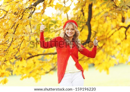 Beautiful young woman in red clothes in autrumn park