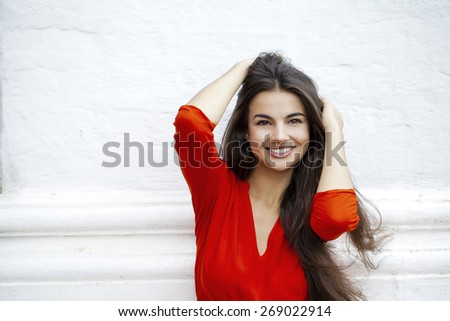 Beautiful young woman in red dress against the background of a block of stone wall - stock photo