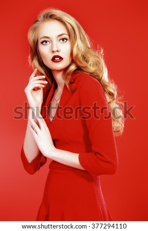 Beautiful young woman in red dress and with blonde curled hair. Beauty, fashion. Cosmetics, make-up. Red background. - stock photo