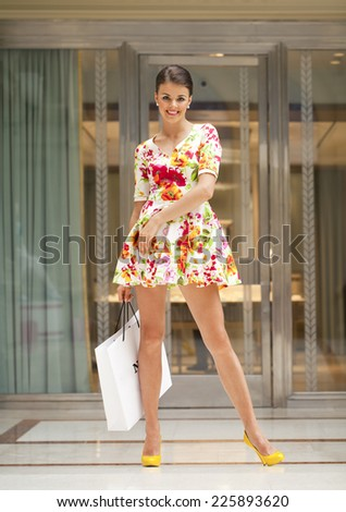 Beautiful young woman in red dress in the shop - stock photo