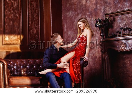 Beautiful young woman in red dress is sitting on sofa and flirting with elegant man in luxury bedroom. - stock photo