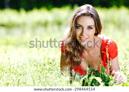 beautiful young woman in red dress lying on grass - stock photo