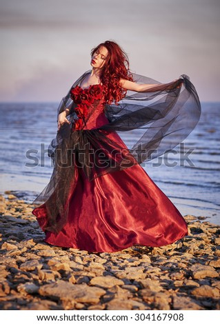 Beautiful young woman in red dress standing on the sea coast - stock photo